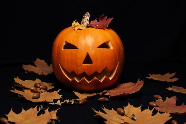 Jack o lantaarnpompoen met oranje herfstesdoornbladeren en eikels Premium Foto