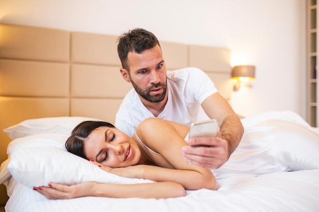 Jaloerse echtgenoot die de telefoon van zijn partner bespioneert terwijl ze thuis in een bed ligt te slapen. Premium Foto