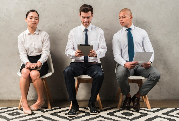 Jaloerse onderneemsterzitting dichtbij de zakenman die digitale tablet gebruiken Gratis Foto