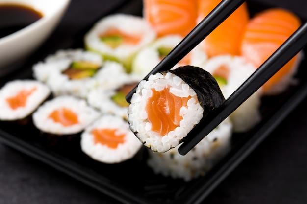Japans voedsel: maki en nigiri sushi op zwarte, dichte omhooggaand worden geplaatst die Premium Foto