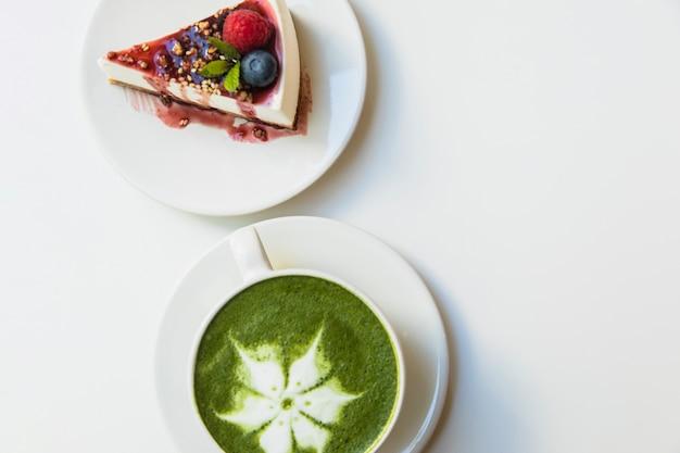 Japanse groene theematcha in witte kop en kaasbescake op plaat over witte achtergrond Gratis Foto