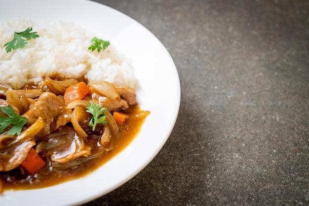 Japanse kerrierijst met gesneden varkensvlees, wortel en uien Premium Foto