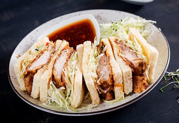 Japanse sandwich met gepaneerde karbonade, kool en tonkatsu saus. Gratis Foto