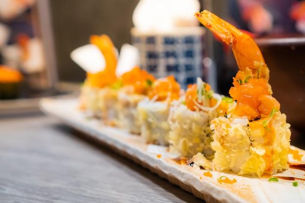 Japanse schotel, crunchy garnalen tempura roll geserveerd op een rechthoekige plaat op houten tafel Premium Foto