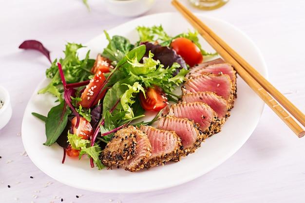 Japanse traditionele salade met stukjes medium-zeldzame gegrilde ahi tonijn en sesam met verse groentesalade op een bord. Gratis Foto