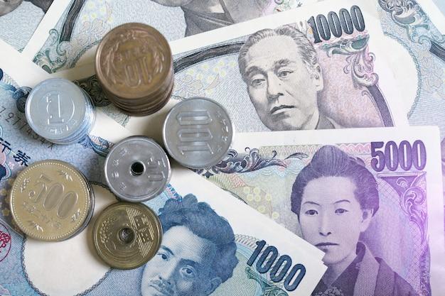 Japanse yen-bankbiljetten en japanse yenmuntstukken voor de achtergrond van het geldconcept. de foto heeft paars licht. Premium Foto