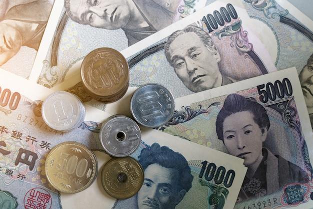 Japanse yen-bankbiljetten en japanse yenmuntstukken voor de achtergrond van het geldconcept Premium Foto