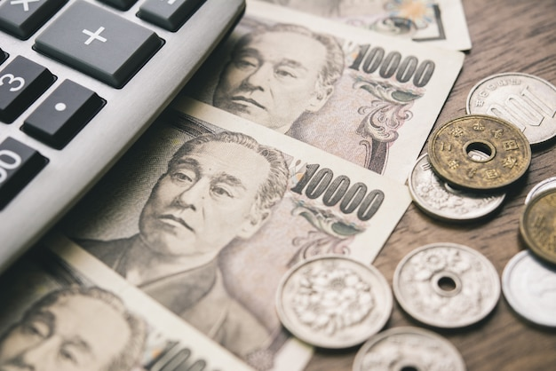 Japanse yen geld rekeningen en munten met calculator op de tafel Premium Foto