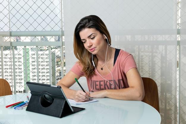 39-jarige vrouw op het balkon van het appartement aan het werk, bij de barbecue en zittend op de bank. Premium Foto