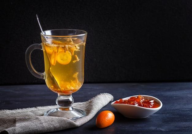 Jasmijnthee met kumquat in een glaskop op een houten raad op een zwarte achtergrond Premium Foto