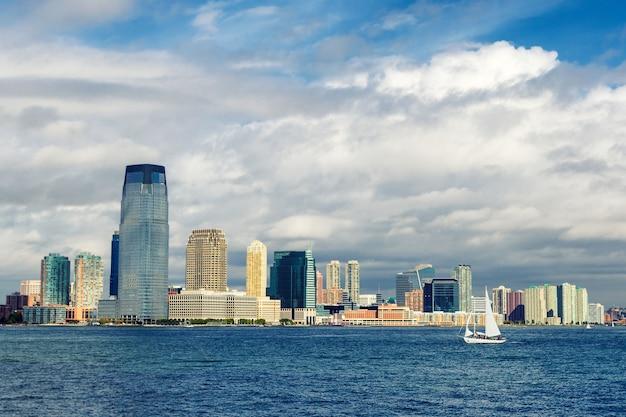 Jersey skyline van de stad en een zeiljacht uitzicht vanaf veerboot Premium Foto