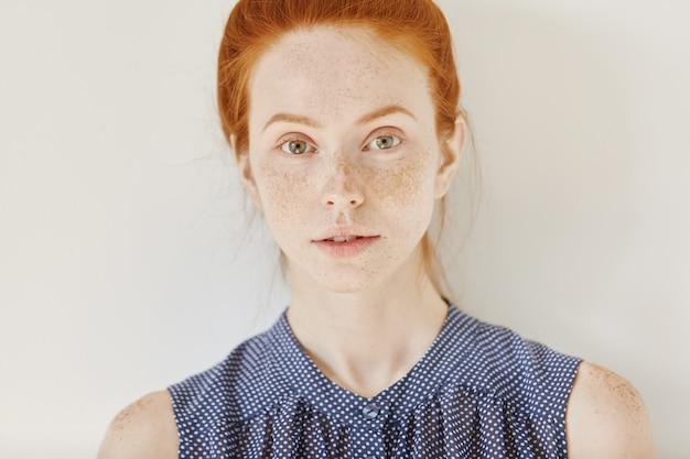 Jeugd en tederheid. sluit omhoog portret van tiener met gemberhaar en gezonde huid met sproeten die mouwloos overhemd met vlekken dragen Gratis Foto