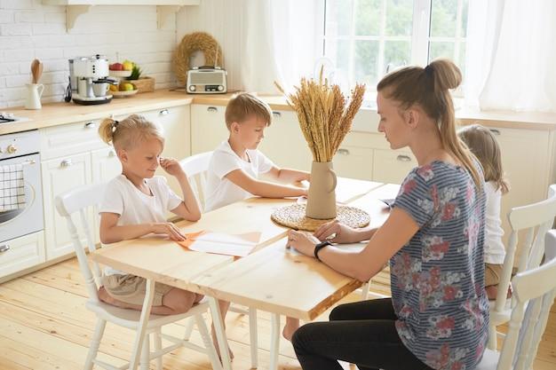 Jeugd, gezin, creativiteit, vrije tijd en hobby-concept. horizontaal schot van jonge terloops geklede moeder die zwangerschapsverlof doorbrengt met haar drie kinderen, samen origami-ambachten maken Gratis Foto