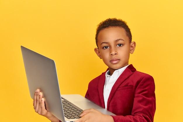 Jeugd, moderne technologie en elektronische gadgets concept. ernstige knappe schooljongen in stijlvolle kleding die generieke laptop met zelfverzekerde blik open houdt, terwijl hij op internet surft terwijl hij huiswerk maakt Gratis Foto