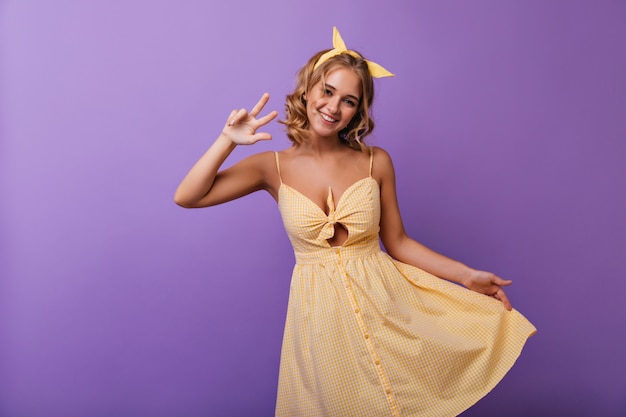 Jocund jonge europese vrouw plezier tijdens de zomer fashion portretshoot. portret van verbazingwekkend krullend meisje in gele kledij. Gratis Foto