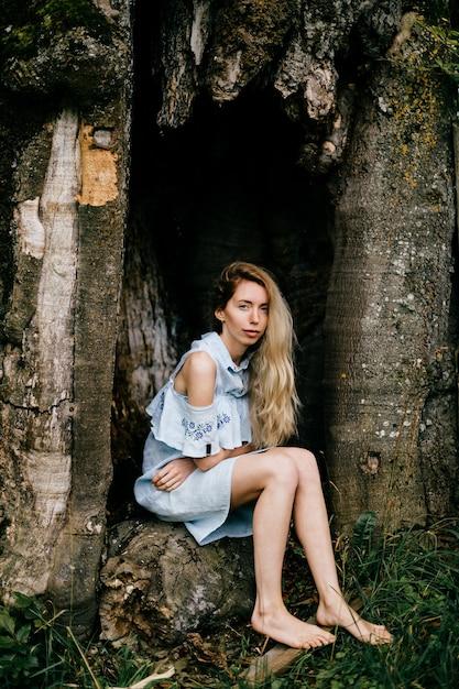Jong aantrekkelijk blootsvoets blondemeisje in blauwe kledingszitting in de oude boom Premium Foto