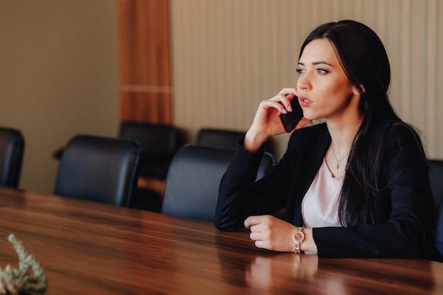 Jong aantrekkelijk emotioneel meisje die in bedrijfsstijlkleren bij bureau met telefoon in bureau of publiek zitten Premium Foto