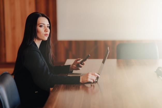 Jong aantrekkelijk emotioneel meisje die in bedrijfsstijlkleren bij een bureau op laptop en telefoon in het kantoor of auditorium zitten Gratis Foto