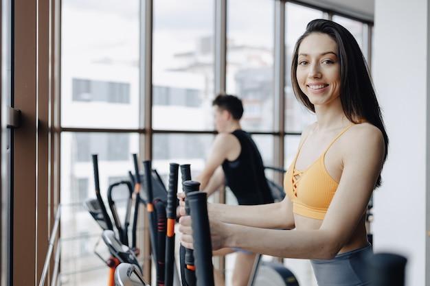 Jong aantrekkelijk meisje bij gymnastiek op hometrainer, fitness en yoga Gratis Foto