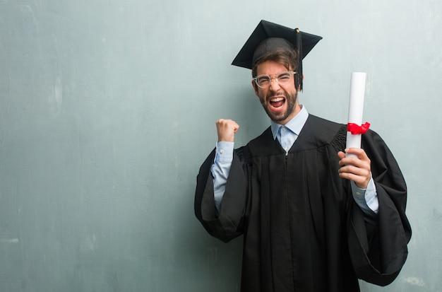 Jong afgestudeerd man tegen een grunge muur met een kopie ruimte erg blij en opgewonden Premium Foto