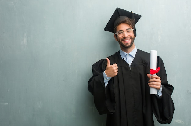 Jong afgestudeerd man tegen een grunge muur met een kopie ruimte vrolijk en opgewonden Premium Foto