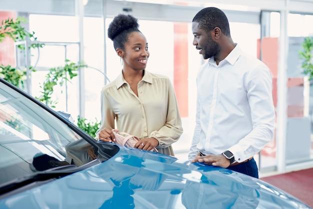 Jong afrikaans getrouwd stel op zoek naar de beste auto bij de dealer Premium Foto