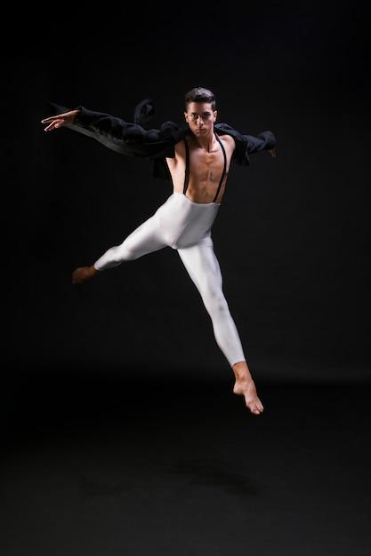 Jong atletisch mannetje dat en op zwarte achtergrond springt danst Gratis Foto