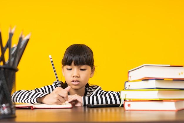 Jong aziatisch jong geitje, het thaise meisje schrijven en nota over lijst met gele achtergrond Premium Foto