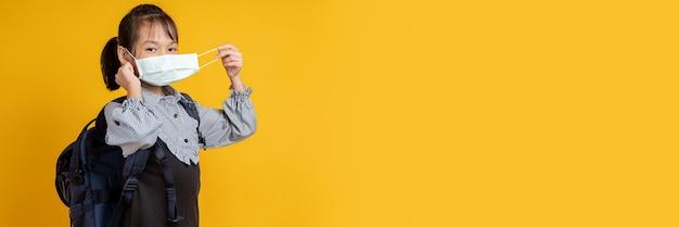 Jong aziatisch meisje dat gezichtsmasker in studio op geel draagt Premium Foto