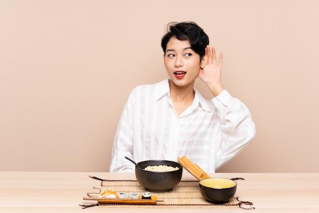 Jong aziatisch meisje in een lijst met kom van noedels en sushi die iets luisteren Premium Foto