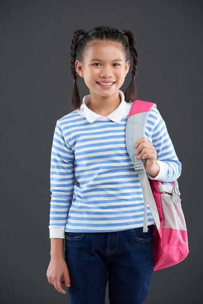 Jong aziatisch meisje in het gestreepte verbindingsdraad stellen met rugzak op één schouder Gratis Foto