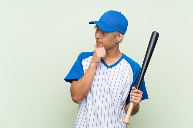 Jong aziatisch mensen speelhonkbal over geïsoleerde groen denkend een idee en kijkend kant Premium Foto