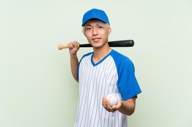 Jong aziatisch mensen speelhonkbal over geïsoleerde groen Premium Foto