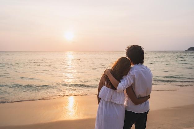 Jong aziatisch paar die mooie zonsondergang op het strand, het concept van de de zomervakantie kijken Premium Foto