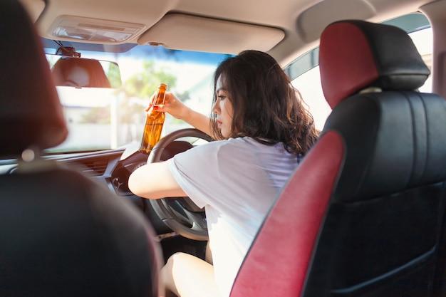 Jong aziatisch vrouw het drinken bier terwijl het drijven van een auto. Premium Foto