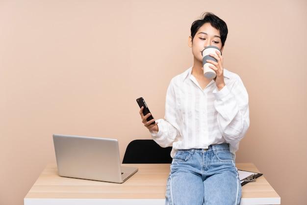Jong bedrijfs aziatisch meisje in haar te nemen koffie van de werkplaatsholding Premium Foto