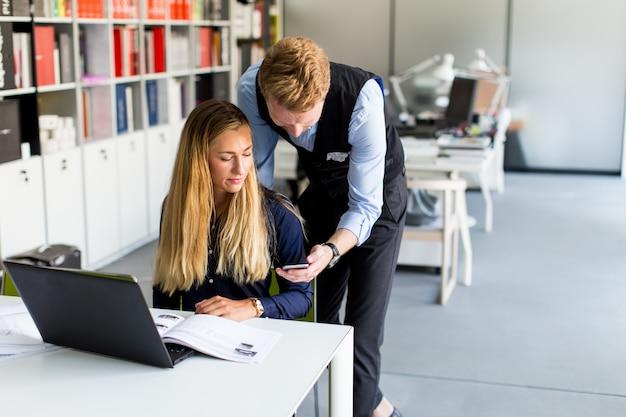 Jong bedrijfspaar die laptop in het bureau met behulp van Premium Foto