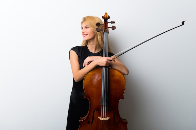 Jong blond meisje met haar cello poseren op witte muur Premium Foto