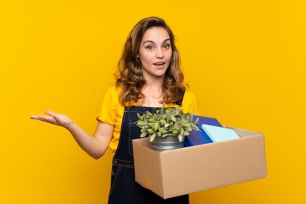 Jong blondemeisje die een beweging maken terwijl het opnemen van een dooshoogtepunt van dingen met geschokte gelaatsuitdrukking Premium Foto