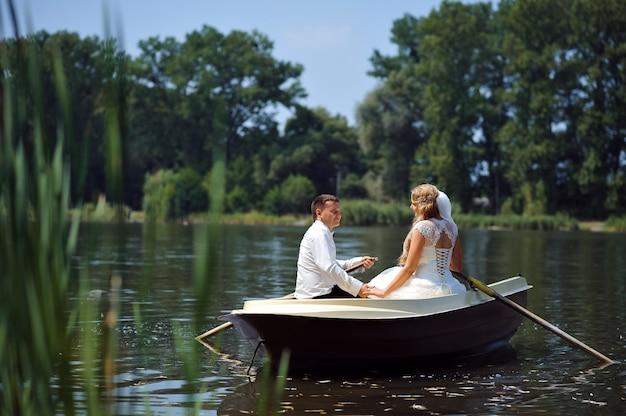 Jong bruidspaar zeilen op de boot Gratis Foto