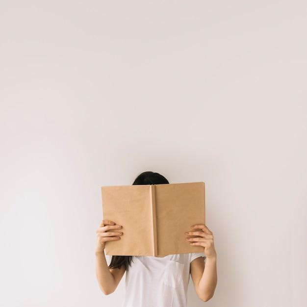 Jong brunette verbergend gezicht achter boek Gratis Foto