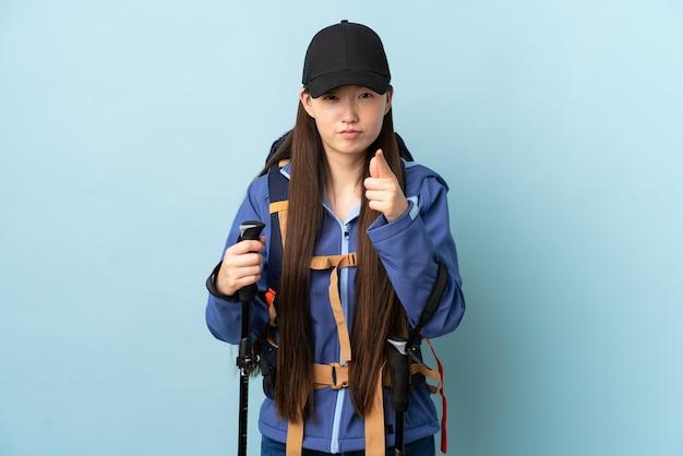 Jong chinees meisje met rugzak en trekking stokken over geïsoleerde blauwe muur gefrustreerd en wijzend naar de voorkant Premium Foto