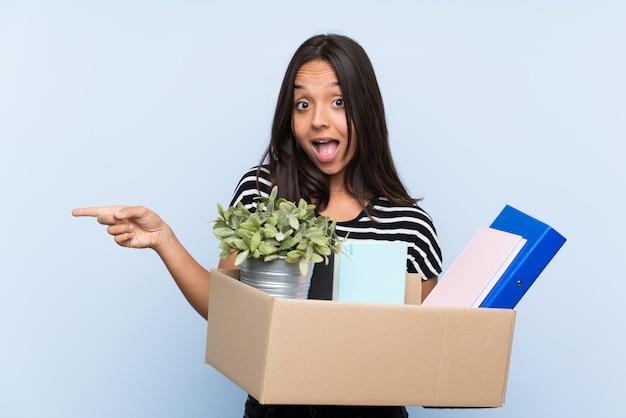 Jong donkerbruin meisje dat een beweging maakt terwijl het oppakken van een doos vol dingen verrast en wijzende vinger naar de kant Premium Foto