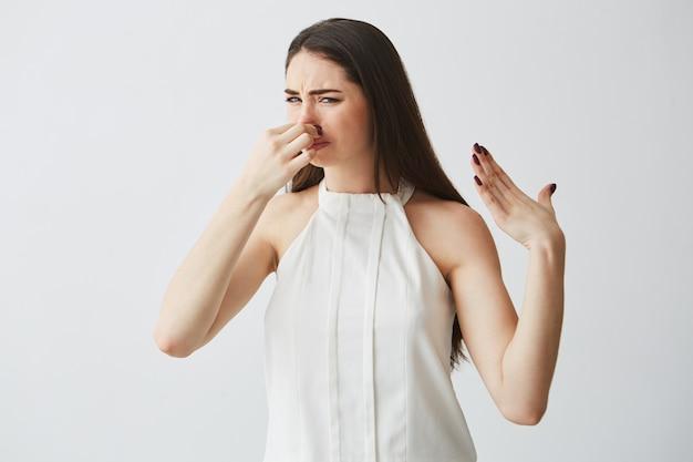 Jong donkerbruin meisje die bedekkende neus sluiten. slechte geur. Gratis Foto
