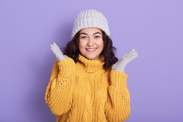 Jong donkerbruin meisje met leuke glimlach die palmen opzij uitspreidt Gratis Foto