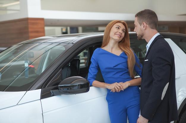 Jong elegant paar die luxueuze auto kopen bij het handel drijven Premium Foto