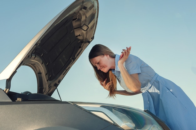 Jong en mooi meisje in de buurt van een kapotte auto met een open kap. problemen met de auto, start niet, werkt niet. Premium Foto