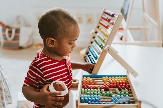 Jong geitje het spelen met een kleurrijk houten telraam Premium Foto