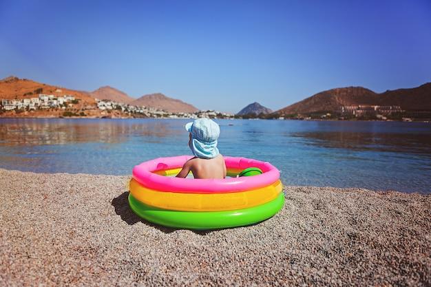 Jong geitje in een glb die dichtbij het overzees op het zwembad van kleine kinderen zitten Premium Foto