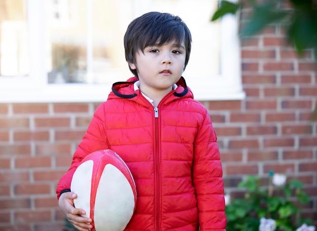 Jong geitjejongen met glimlachend speelrugby in zonnige dagochtend, de lente of de zomersport voor jonge kinderen Premium Foto